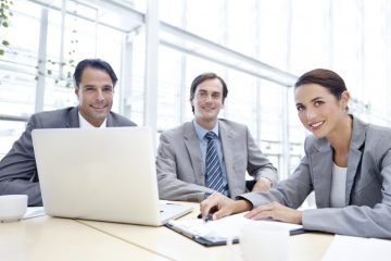 Three co-workers smiling at the camera while sitting behind a desk with a laptop and documents in front of them