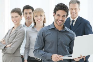 Happy business man holding a modern laptop computer with his team in background